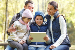 Family sitting on bench with tablet pc at camp Stock Image