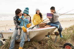 Family Sitting On Boat With Fishing Rod On Beach. Family Group Sitting On Boat With Fishing Rod On Winter Beach royalty free stock photography
