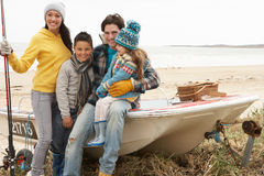 Family Sitting On Boat With Fishing Rod On Beach. Family Group Sitting On Boat With Fishing Rod On Winter Beach stock photography