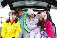 Family Sitting In Boot Wearing Winter Clothes. Teenage Family Sitting In Boot Of Car Wearing Winter Clothes All Laughing Royalty Free Stock Photography