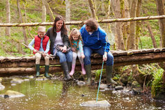 Family Sitting On Bridge Fishing In Pond With Net Royalty Free Stock Images