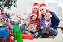 Family Sitting By Christmas Gifts Stock Photo