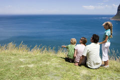 Family sitting on clifftop edge, looking at Atlantic Ocean horizon, rear view Stock Image