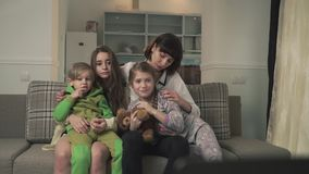 Family sitting on the couch in the guest room and watching TV emotionally. Older sisters and younger kids spend time stock video footage