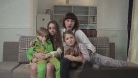 Family sitting on the couch in the guest room and watching TV expressive and emotionally. Older sisters and younger stock video footage