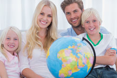 Family sitting on couch holding globe Royalty Free Stock Photo