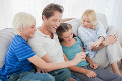 Family sitting on a couch and looking at a photo Stock Photography