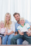 Family sitting on couch playing video games. In the living room stock photos