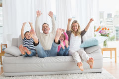 Family sitting on a couch and raising arms Royalty Free Stock Photo