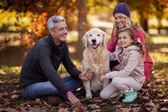 Family sitting with dog at park Royalty Free Stock Photo