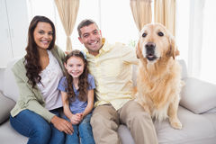 Family sitting with dog on sofa Royalty Free Stock Photo