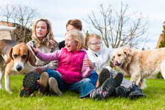 Family sitting with dogs together on a meadow Royalty Free Stock Photo