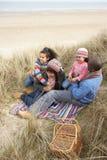 Family Sitting In Dunes Enjoying Picnic Royalty Free Stock Photo