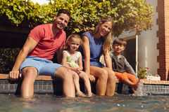 Family sitting with feet in swimming pool. Young family of four sitting on edge of their pool looking at camera on a sunny day royalty free stock image