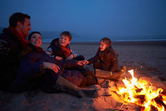 Family Sitting By Fire On Winter Beach Royalty Free Stock Photo