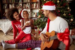 Family sitting on floor together and listening guitar songs at h. Happy family sitting on floor together and listening guitar songs at home on Christmas royalty free stock image