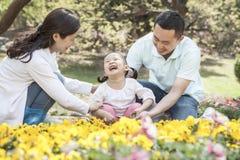 Family sitting in flower garden. Stock Images
