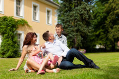 Family sitting in front of their home Stock Image