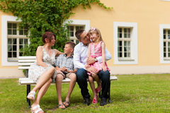 Family sitting in front of their home Stock Images
