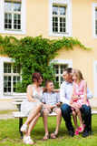 Family sitting in front of their home Royalty Free Stock Photos