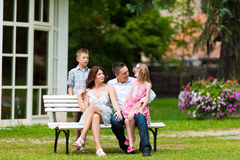 Family sitting in front of their home Royalty Free Stock Photo