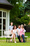 Family sitting in front of their home Stock Photo