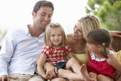 Family Sitting  On Garden Seat Together Royalty Free Stock Photos