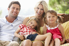 Family Sitting  On Garden Seat Together Royalty Free Stock Photography