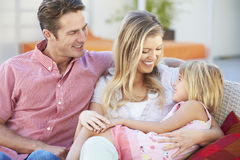 Family Sitting  On Garden Seat Together Royalty Free Stock Image