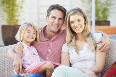 Family Sitting  On Garden Seat Together Royalty Free Stock Photo