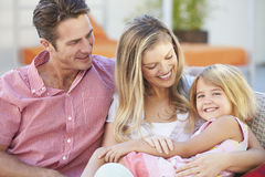 Family Sitting  On Garden Seat Together Stock Photography