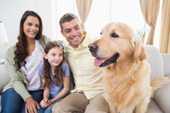Family sitting with Golden Retriever on sofa Royalty Free Stock Photography