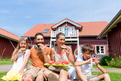Family sitting in grass front of home eating water melon Royalty Free Stock Photography