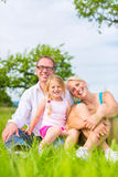 Family sitting on grass of lawn or field Royalty Free Stock Photos