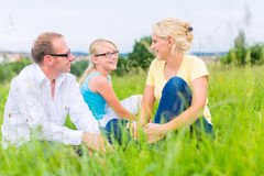 Family sitting on grass of lawn or field Royalty Free Stock Images