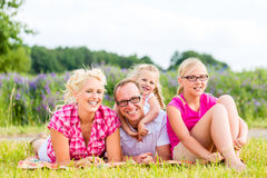 Family sitting on grass in lawn or field Royalty Free Stock Photos