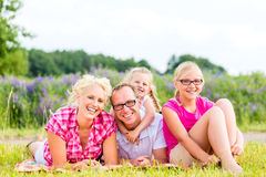 Family sitting on grass in lawn or field Stock Photos