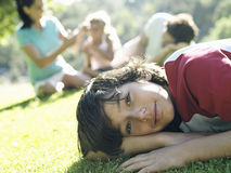Family sitting on grass in park, focus on boy (10-12) in foreground, portrait, surface level (tilt) Stock Photography