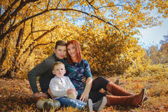 Family sitting on a grass with pumpkin. In autumn forest Stock Photo