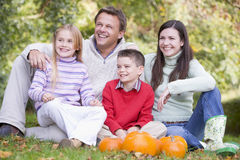 Family sitting on grass with pumpkins smiling royalty free stock image