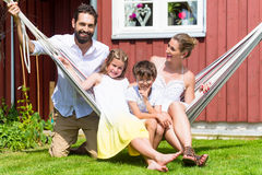 Family sitting in hammock in front of home Royalty Free Stock Photography