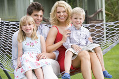 Family sitting in hammock smiling Stock Photos