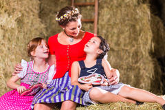 Family sitting on hayloft with gingerbread Royalty Free Stock Image