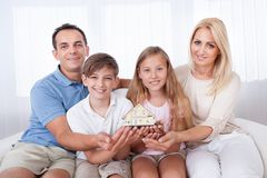 Family Sitting Holding Miniature Model Of House. Family With Two Children Sitting On Couch Holding Miniature Model Of House At Home royalty free stock photo