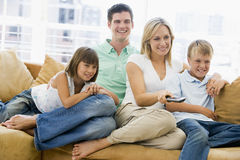 Family Sitting In Living Room With Remote Control Stock Photography