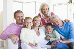 Family sitting indoors smiling Royalty Free Stock Photos