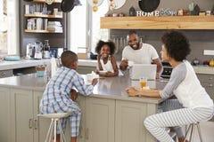 Family Sitting In Kitchen Enjoying Morning Breakfast Together royalty free stock image