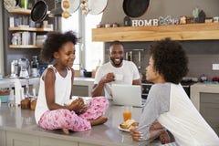 Family Sitting In Kitchen Enjoying Morning Breakfast Together stock photos