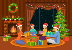 Family sitting in living room on the floor at fireplace and decorated christmas tree, exchanging xmas presents. Royalty Free Stock Photo