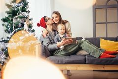 Family sitting in living room having fun with tablet that Santa Claus brought. Family gathered around a Christmas tree, using a tablet Royalty Free Stock Images